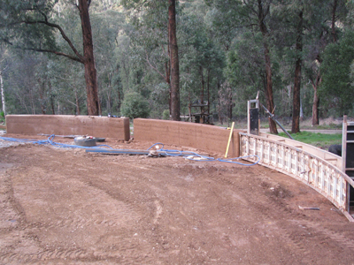 Sections of curved rammed earth begin to form the outdoor feature wall