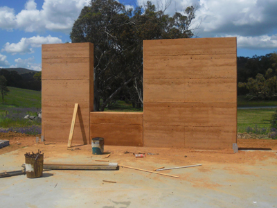A rammed earth window section between two walls