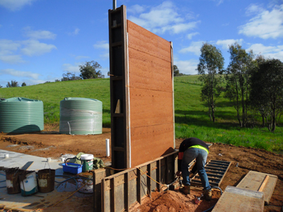 Stripping the rammed earth formwork after lifts have been completed and soil mix has began to cure